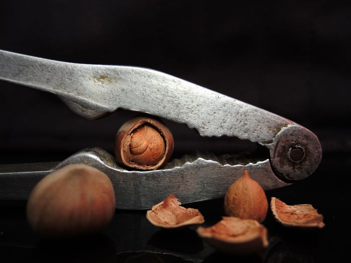 Close-up of nuts and nutcracker against black background