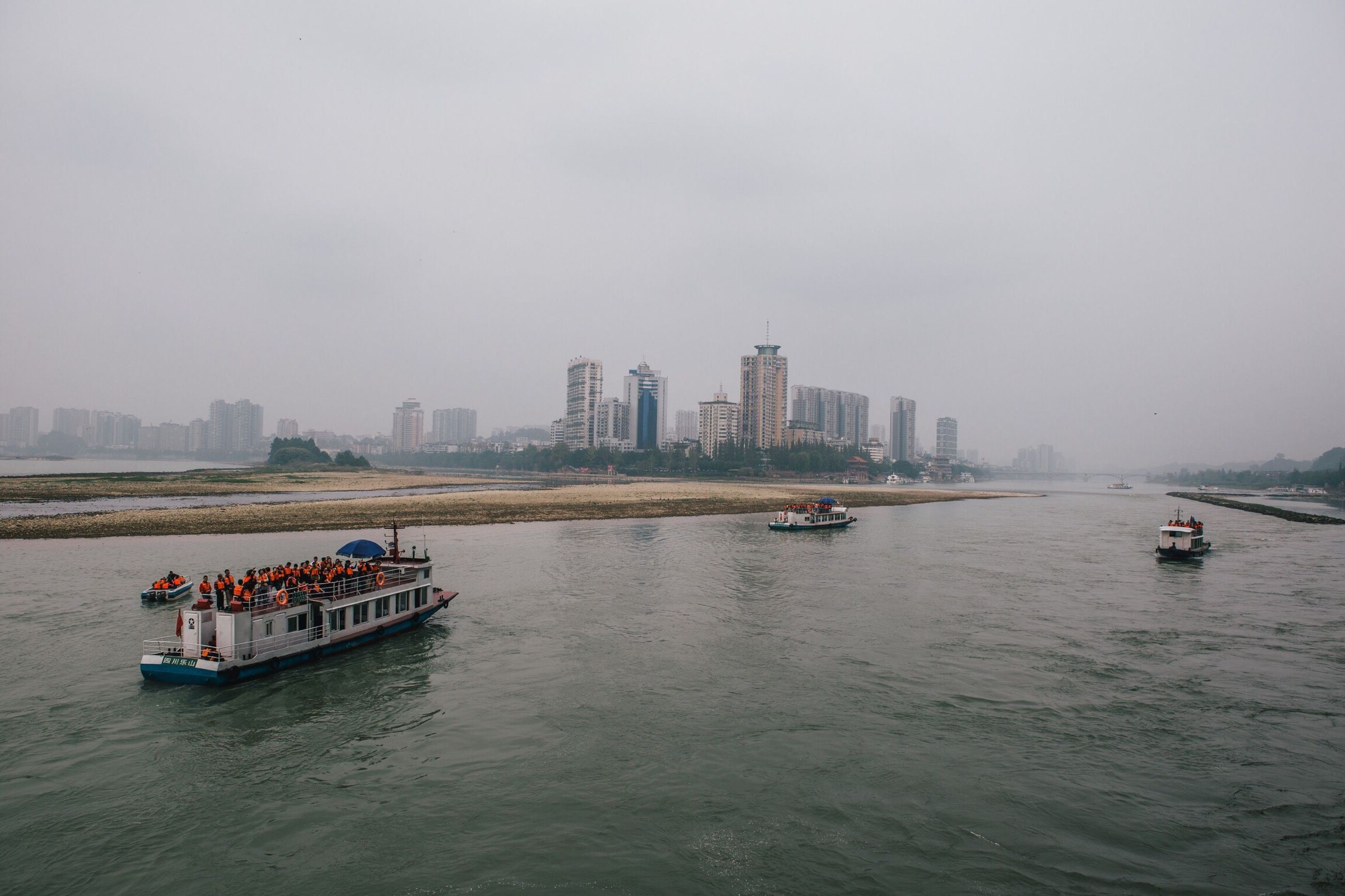 nautical vessel, transportation, boat, mode of transport, water, river, waterfront, building exterior, architecture, city, skyscraper, ferry, sailing, sky, urban skyline, passenger craft, ship, day, tall, barge, journey, city life