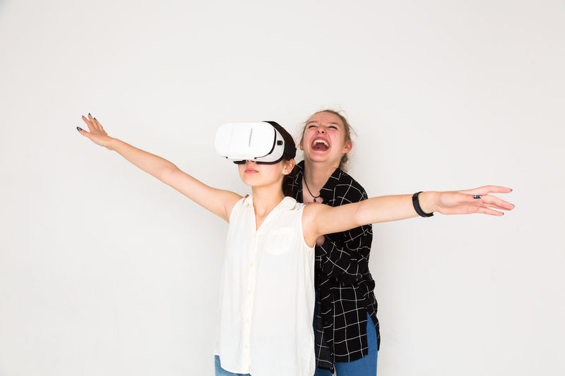 Laughing enjoying virtual reality experience with open arms 3D Augmented Reality Enjoyment Entertainment Friendship Full Frame Fun Futuristic Game Happiness Head Mounted Display Hm HMD Leisure Activity Recreational Pursuit Smiling Studio Shot Three Dimensional Two People Virtual Reality Headset Virtual Reality Simulator Vr White Background Young Adult Young Women The Portraitist - 2017 EyeEm Awards Rethink Things AI Now