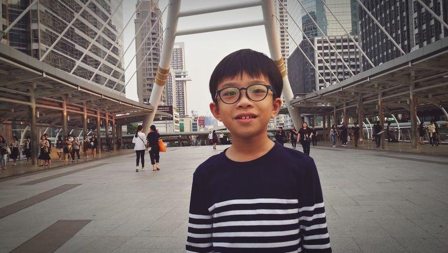 Portrait Of Boy Standing On Footpath In City