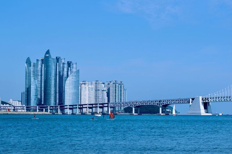 Bridge over sea against buildings in city