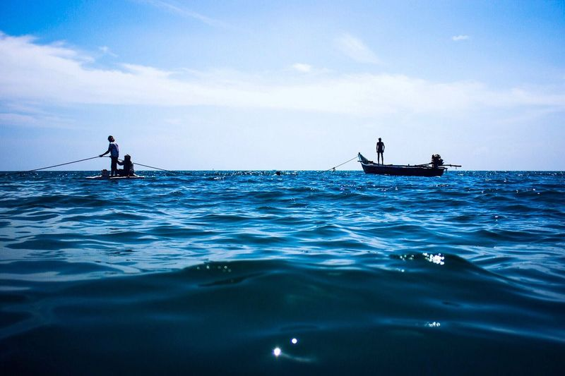 Fishermen in sea against sky