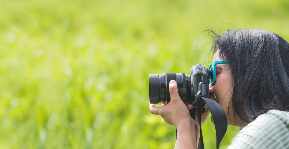 Side view of woman photographing with camera on field