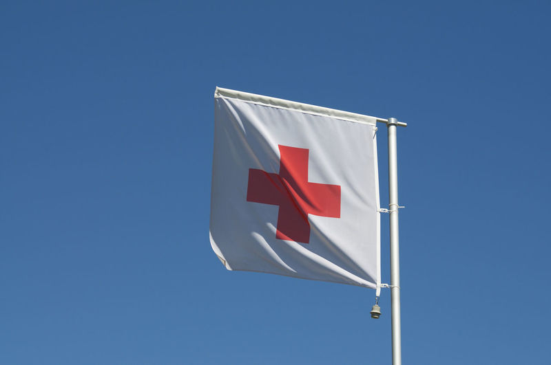 The flag of international red cross and red crescent movement against a blue sky in switzerland