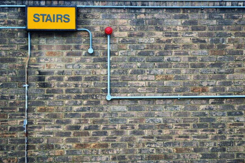 Stairs Sign On Brick Wall With Pipes