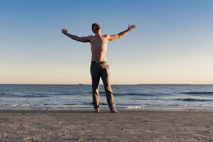 Shirtless man at the beach at sunset raising his arms to the sky looking up in vivid color. Glory To God  Arms Raised Arms Raised Arms Outstretched Human Beach Beauty In Nature Clear Sky Fitness Full Length Healthy Eating Horizon Over Water Leisure Activity Lifestyles Men Nature One Person Outdoors Prayer Real People Religion Scenics Sea Sky Standing Vivid Color Water #FREIHEITBERLIN