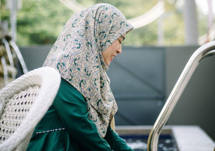 Woman in hijab sitting outdoors