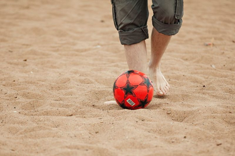 Low Section Of Man Playing Soccer On Sand At Beach