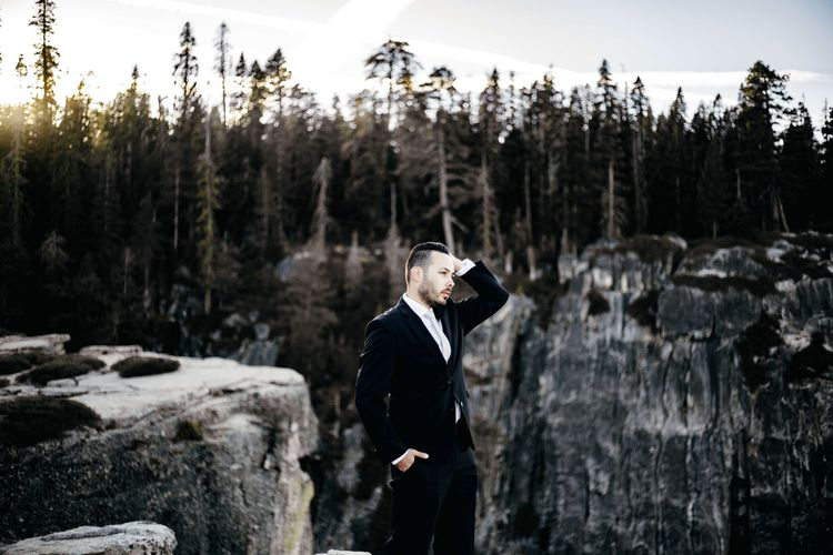 Man looking away while standing against trees