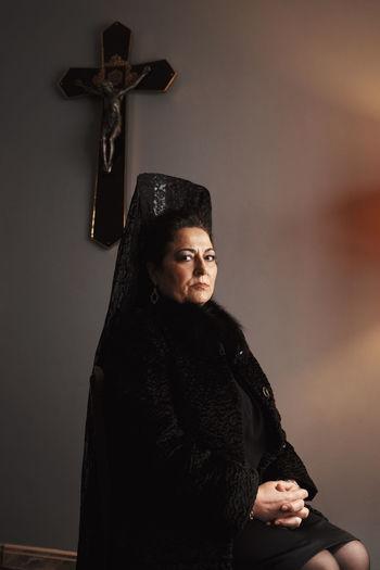 Nun praying against cross at home