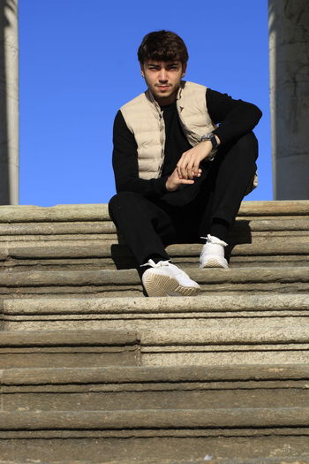 Low angle portrait of young man sitting on staircase