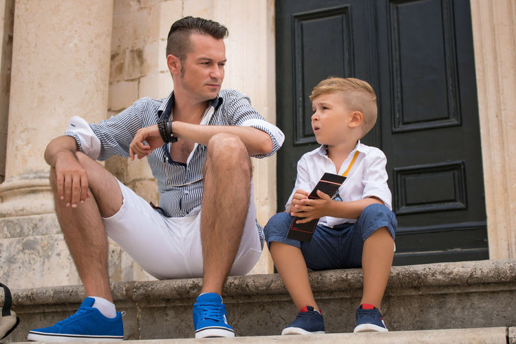 Full length of father with son sitting on staircase