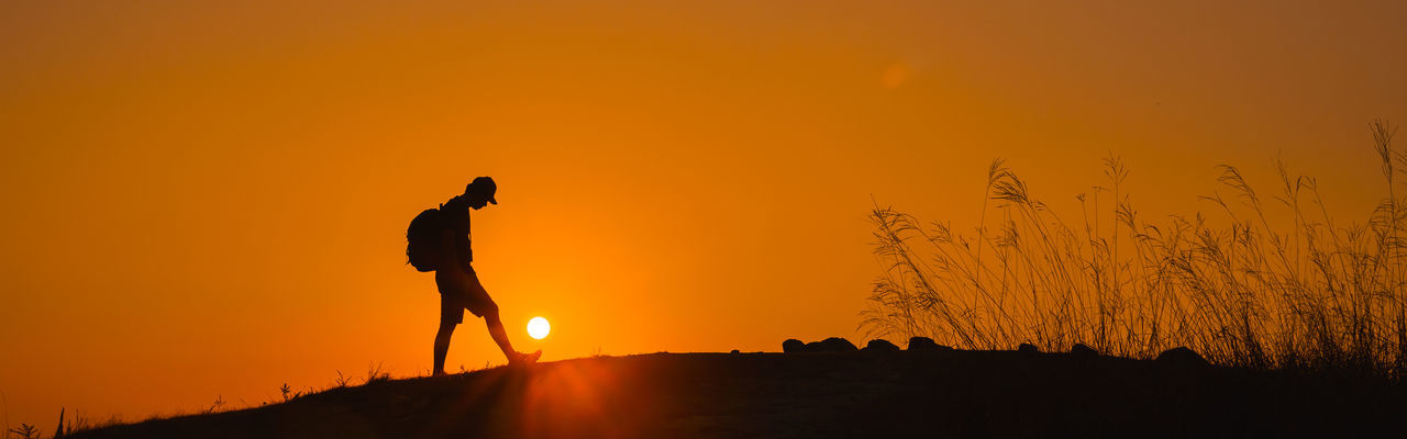 Silhouette person standing on land during sunset
