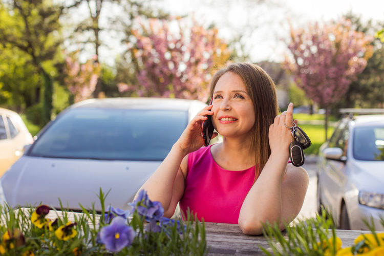 Portrait of smiling young woman using phone while sitting on car