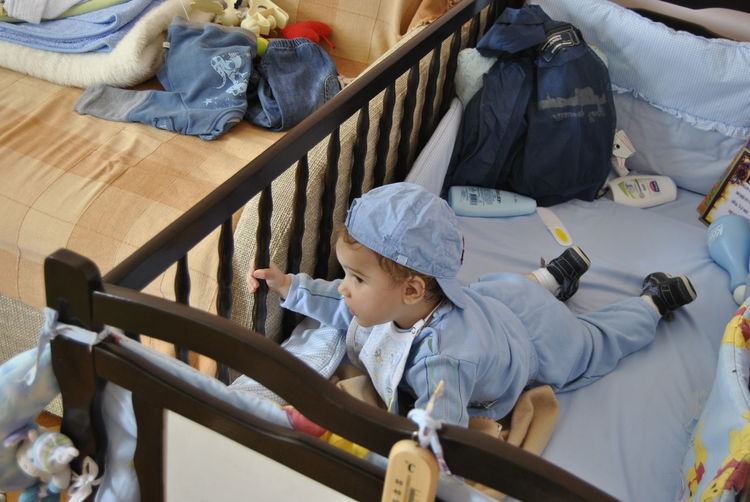 High angle view of baby boy relaxing on crib at home