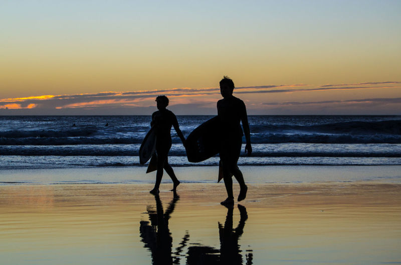 Silhouette men with surfboards walking at beach during sunset
