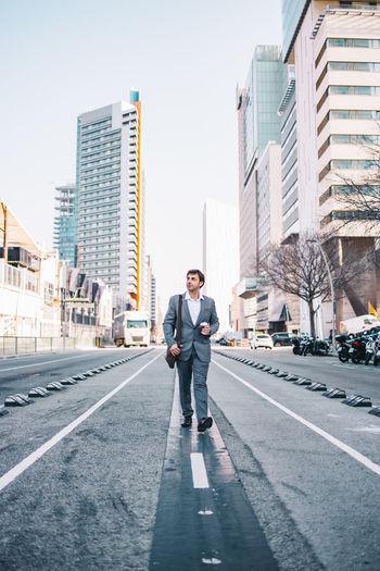 Full length of businessman walking on road against building