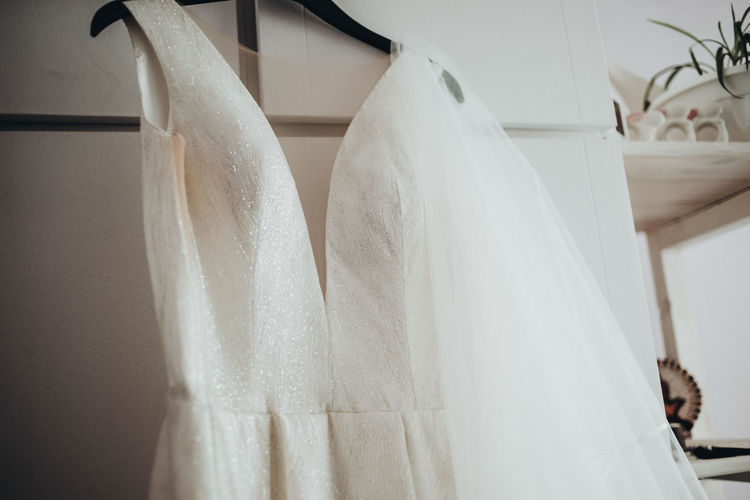 Low angle view of wedding dress hanging on cabinet