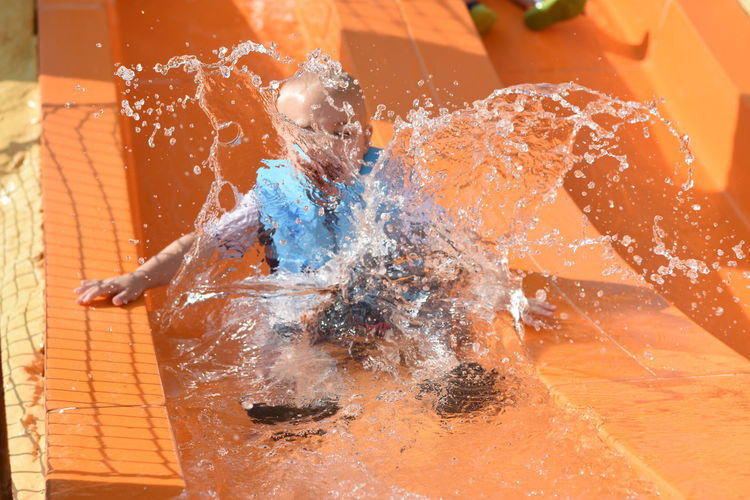Close-up of child on water slide
