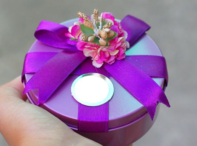 Give a violet round gift box with purple ribbon and a flower Gift Round Violet Purple Hand Holding Sending Give Giving Season Of Giving Ribbon Bow Receiving Receive Celebrate Special Tag Card Space Christmas New Year Birthday Beautiful Pretty