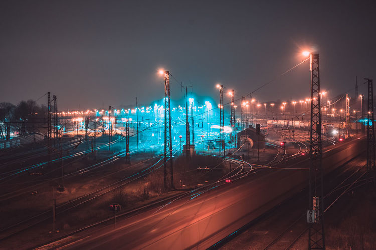 High angle view of illuminated railroad tracks against clear sky at night