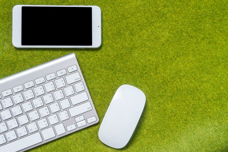 High Angle View Of Keyboard And Mobile Phone On Grass