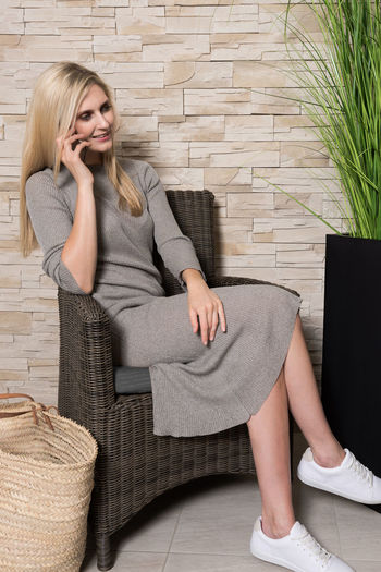 Full Length Of Beautiful Woman In Dress Sitting While Talking On Phone At Home