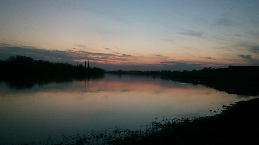 Scenic shot of calm countryside lake at sunset