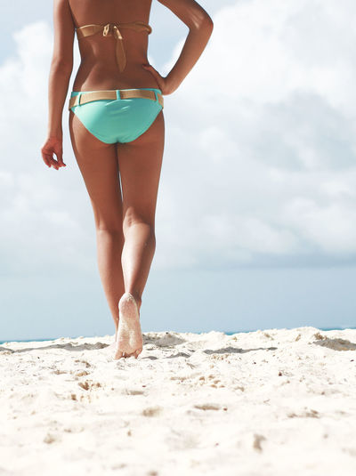 Rear view of young woman in bikini posing on beach against sky