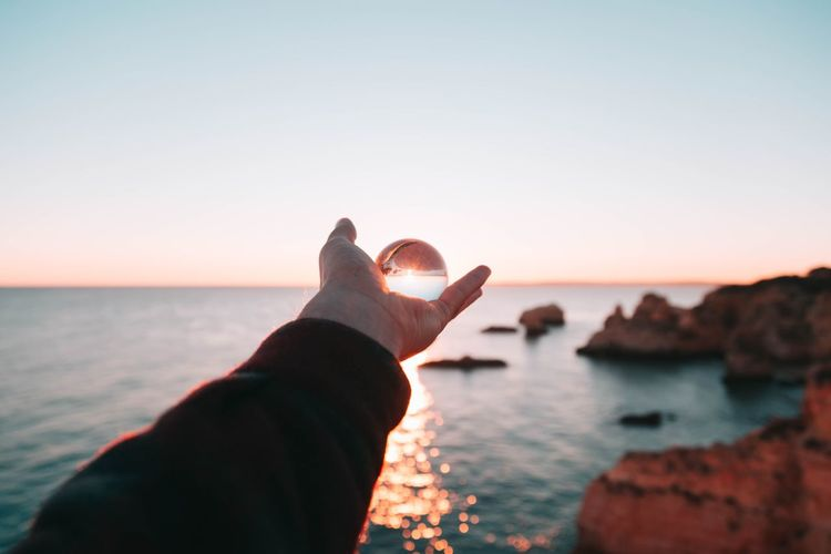 Close-up of hand against sea during sunset