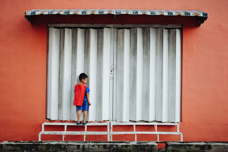 Boy standing against red wall