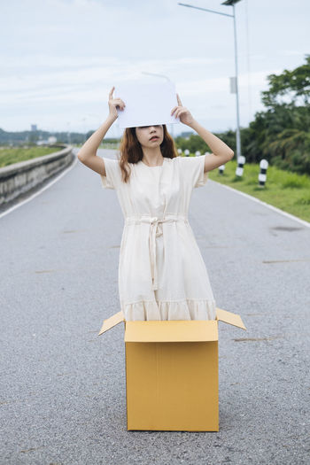 Young woman holding placard while standing in cardboard box on road