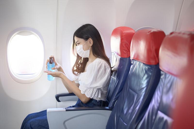 Woman wearing mask using hand sanitizer while sitting at airplane