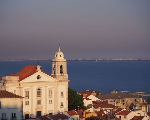 View from Miradouro das Portas do Sol in Lisbon, Portugal. Church Houses Lisboa Portugal Miradouro Das Portas Do Sol Architecture Bell Tower Building Exterior Built Structure City Cityscape Golden Hour Horizon Over Water Lisboa Miradouro Place Of Worship Religion Roofs Sea Spirituality Sunset Sunshine Urban View From Above Water Waterfront