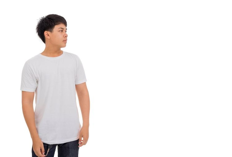 An Asian man in white casual and blue jeans is looking to the blank space aside. Standing Hands Chin Look For Look Up Look Aside Shoulder Young Adult Handsome Thai Man Man Strong Healthy Asian Man White Shirt Copy Space Standing White Background Copy Space Young Adult Studio Shot Casual Clothing Young Men Looking Three Quarter Length Males  T-shirt Looking Away Lifestyles Teenager