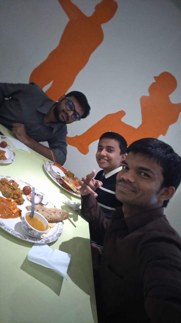 food and drink, food, table, plate, mid adult men, men, friendship, meal, togetherness, real people, serving size, smiling, fork, ready-to-eat, group of people, happiness, lifestyles, eating, service, sitting, women, drink, indoors, healthy eating, freshness, young adult, day, people