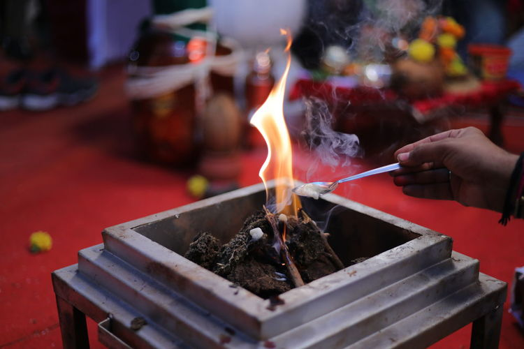 Person holding lit candles in temple