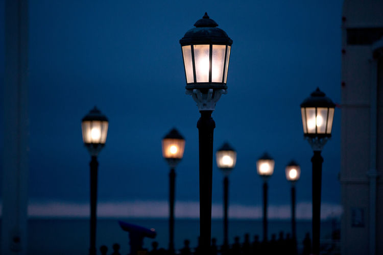 Illuminated street lamps against blue sky at night