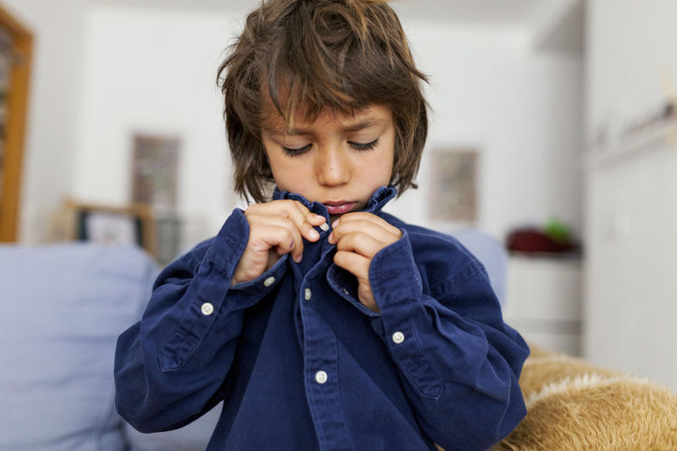 Boy looking away while standing at home