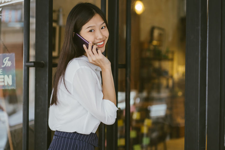 Portrait of Asian girl enter door to coffee shop .Businesswoman using phone and walking to cafe Asian  Asian Girl Woman Female Girl Young Women Young Adult Thailand Japanese  Korean Taiwanese Taiwan Beauty Beautiful Beautiful Woman Cute Relaxing Women Lady Portrait Smart Phone Call PhonePhotography Talking Business Business Person Businesswoman Smiling Coffee Shop Cafe One Person Standing Real People Waist Up Focus On Foreground Lifestyles Leisure Activity Using Phone Casual Clothing Holding Telephone Side View Communication Happiness Wireless Technology Hairstyle