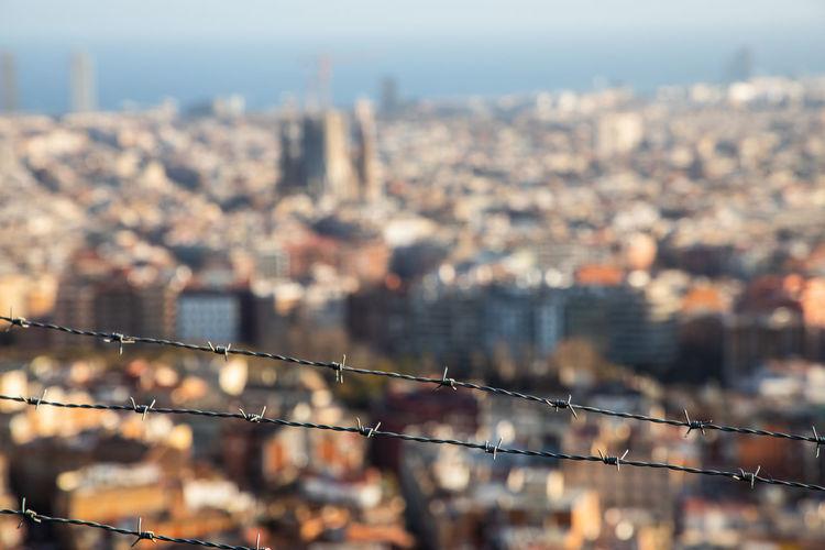 Cityscape seen through fence against sky