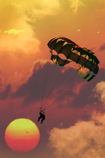 Composite image of a sunset and a couple paragliding over Hampton beach, NH Adventure Cloud - Sky Day Extreme Sports Flying Leisure Activity Lifestyles Low Angle View Men Mid-air Nature Orange Color Outdoors Parachute Paragliding People Real People Silhouette Sky Skydiving Sport Sun Sunset