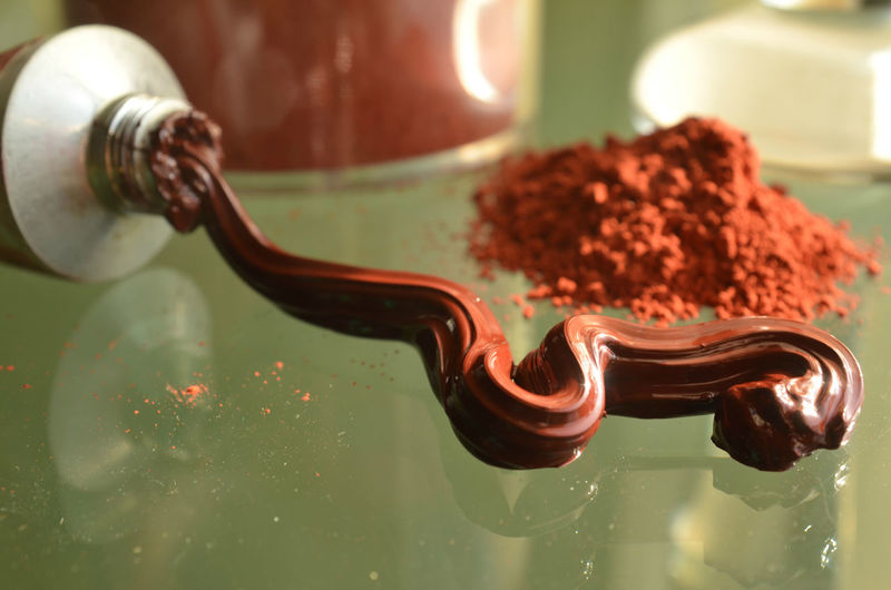 Earth red dry pigment powder and glass paint muller and tube of red squeezed out oil paint