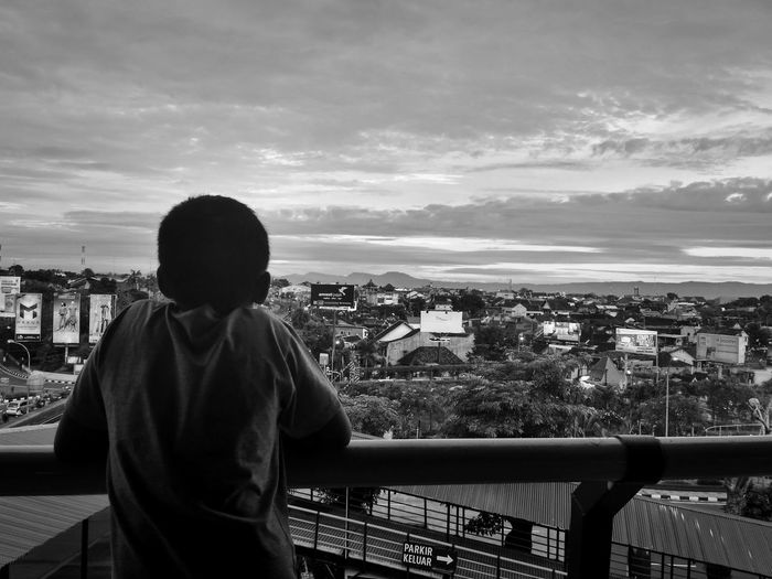 Rear view of boy looking at city from observation tower