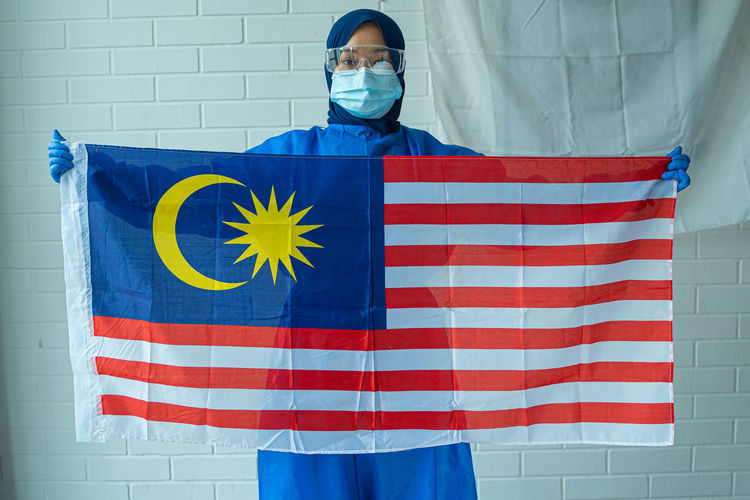 Portrait of doctor holding malaysian flag against wall