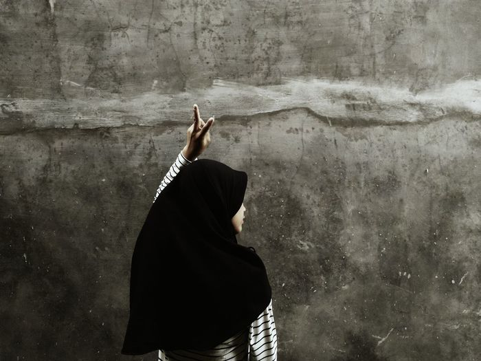 Rear view of woman gesturing peace sign while standing against wall