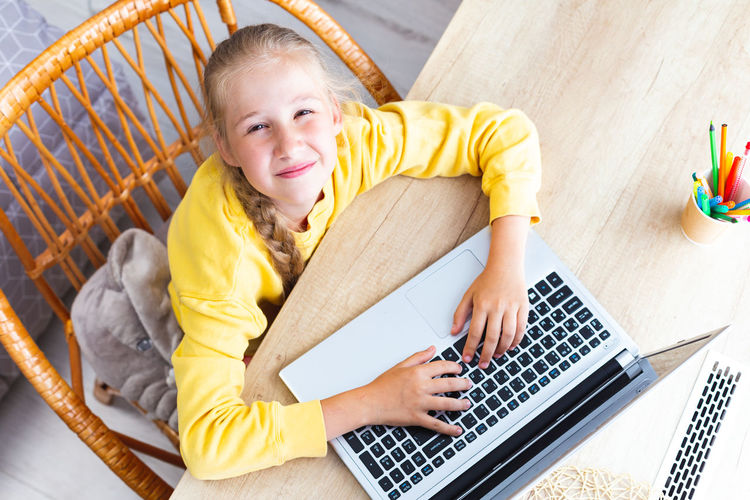 Caucasian girl 10-11 years, hands on laptop keyboard, squinting eyes, top view.