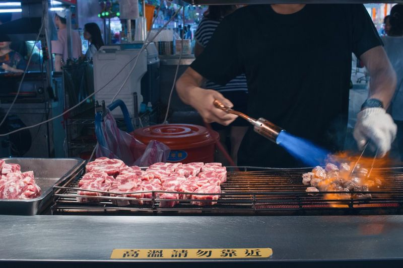 Man working on barbecue grill at market
