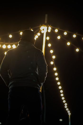 Rear view of man standing against illuminated lights