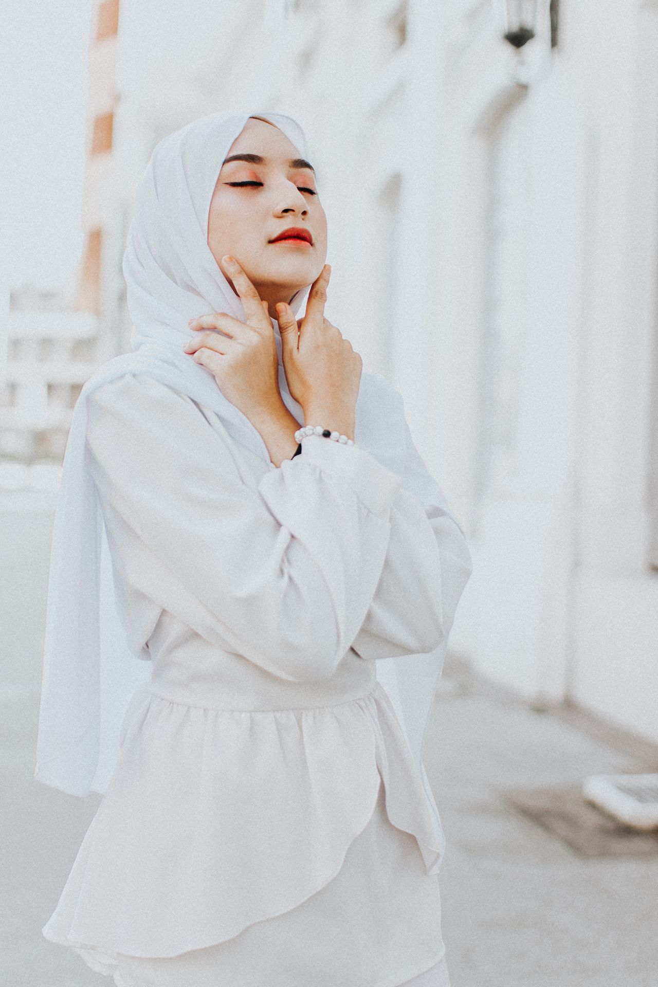Beautiful young woman wearing hijab while standing against building